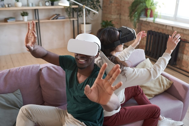 Молодая возбужденная пара в очках сидит на диване спиной к спине и играет дома в видеоигры