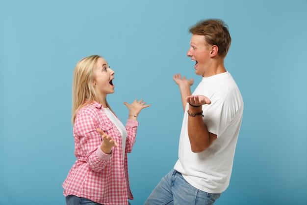 Молодая возбужденная пара два друга парень девушка в белой розовой пустой дизайнерской футболке позирует