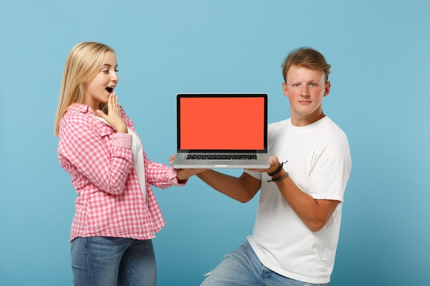 Молодая взволнованная пара, двое друзей, мужчина и женщина в белых розовых футболках, позируют