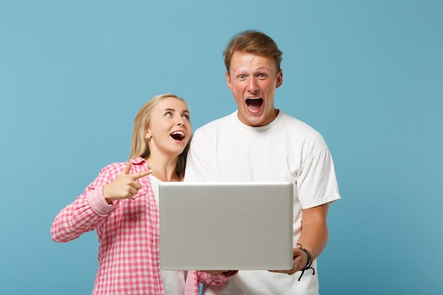 Young excited couple two friends man and woman  in white pink empty blank t-shirts posing