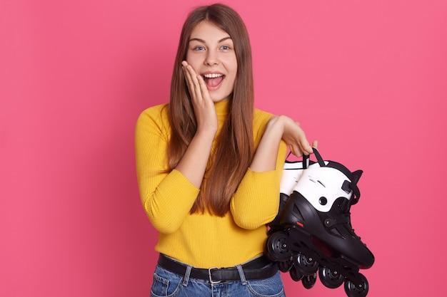 Молодые возбужденные девушки носить желтую рубашку и джинсы, держа роликовые коньки, касаясь ее щеки, позирует с раскрытой пасти, изолированные на розовой стене.