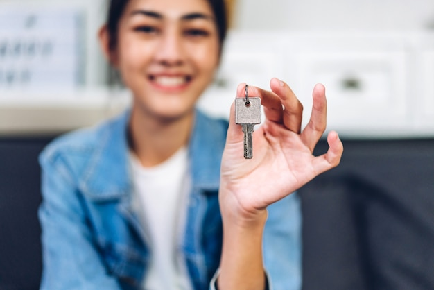 Young excited happy asian woman holding new house key in their hands and buying a new home and are moving.business and real estate concept