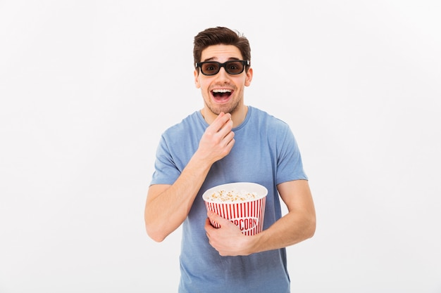 Young excited man in casual t-shirt and 3d glasses holding bucket with popcorn and , isolated over white wall