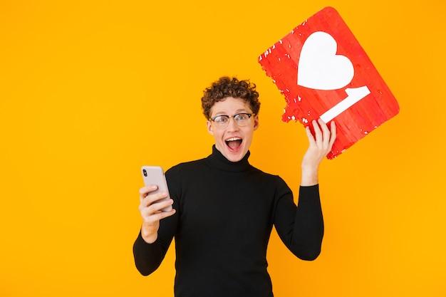 플래카드를 들고 노란색으로 격리된 휴대폰을 사용하는 안경을 쓴 흥분한 젊은이