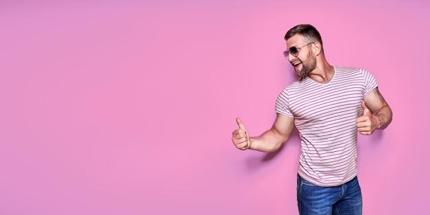 분홍색 배경 위에 휴가 중인 젊은 흥분한 남자가 성공적인 아이디어를 가지고 옆으로 손가락을 가리키고 있다