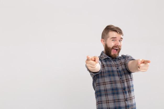 ひげを生やした若い興奮した男、コピースペースのある白い壁に指を正面に向ける