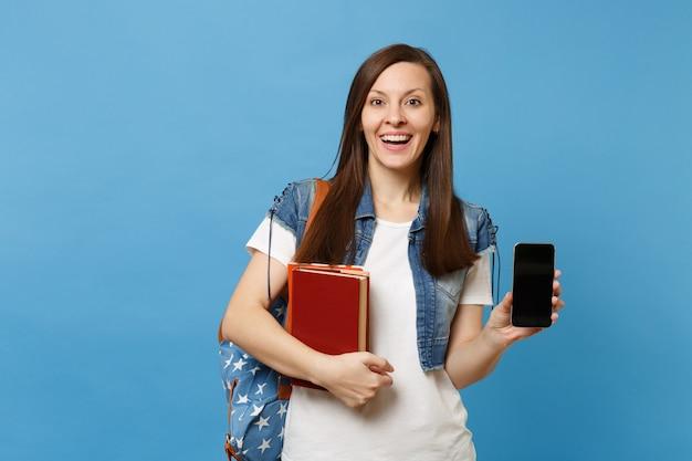 배낭을 메고 데님 옷을 입은 젊고 흥분된 예쁜 여학생은 파란색 배경에 격리된 빈 검은색 빈 화면이 있는 학교 책 휴대전화를 들고 있습니다. 고등학교 대학 대학에서 교육.