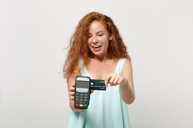 젊은 흥분된 빨간 머리 여자에 고립 된 흰색 배경 포즈. 사람들이 라이프 스타일 개념입니다. 복사 공간을 비웃습니다. 처리할 무선 현대 은행 결제 단말기를 들고 신용 카드 결제를 획득합니다.