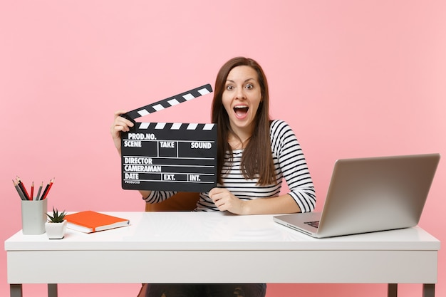 Young excited woman hold classic black film making clapperboard working on project while sit at office with laptop isolated on pastel pink background. achievement business career concept. copy space.