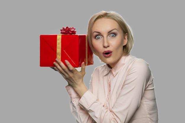 선물 상자를 들고 젊은 흥분된 여자. 그녀의 생일 선물을 기뻐하는 젊은 충격 된 백인 여자.