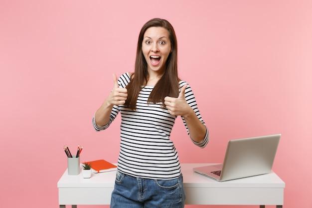 パステルピンクの背景で隔離のラップトップと白い机の近くに立って親指を立てる仕事を示すカジュアルな服を着た若い興奮した女性。業績ビジネスキャリアコンセプト。広告用のスペースをコピーします。
