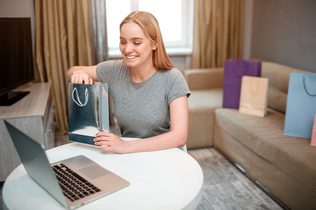 Young excited woman is unboxing her parcel while sitting at the table