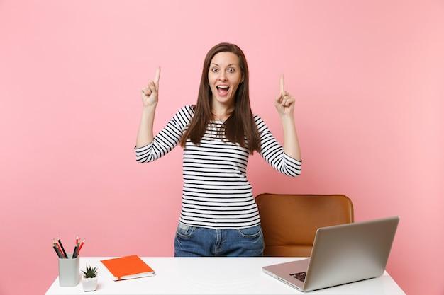 人差し指を指して仕事をして、パステルピンクの背景に分離されたpcラップトップで白い机の近くに立っている若い興奮した女性。業績ビジネスキャリアコンセプト。広告用のスペースをコピーします。