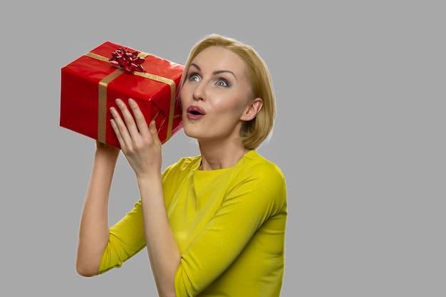 젊은 흥분된 여자 떨고 선물 상자. 젊은 충격 된 백인 여자 그녀의 생일 선물 상자를 기뻐.