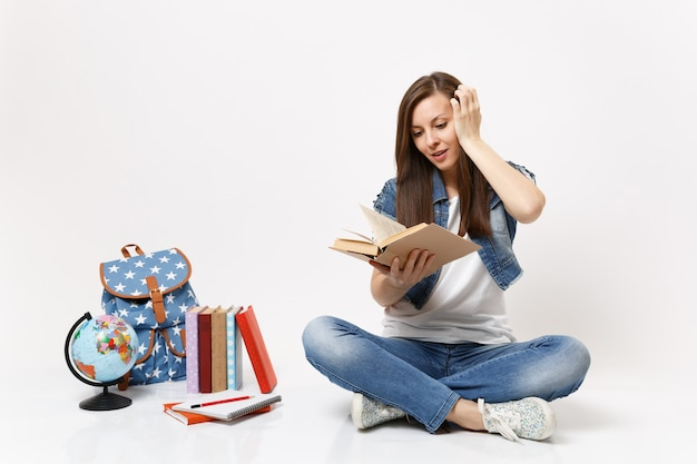 Young excited woman student in denim clothes hold book read keeping hand near head sitting near globe, backpack, school books isolated on white wall