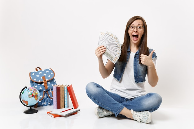 Young excited woman student holding bundle lots of dollars, cash money showing thumb up sit near globe, backpack school books isolated on white wall