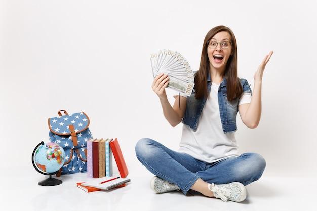 Молодая взволнованная студентка держит пачку долларов, раскидывает руки наличные деньги, сидя возле рюкзака глобуса, изолированные школьные учебники