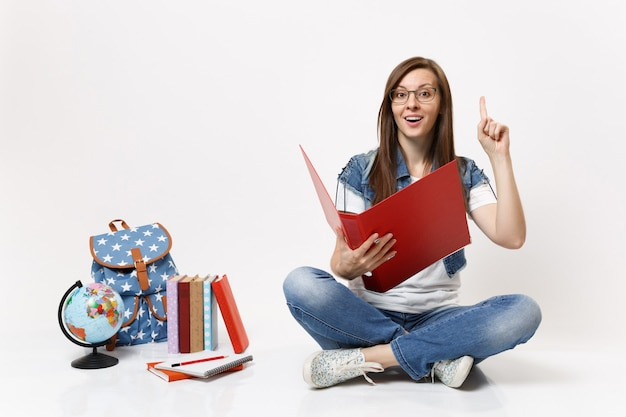 Young excited woman student holding red folder for papers document pointing index finger up near globe backpack, school books isolated