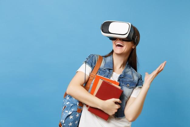 Молодая взволнованная студентка в джинсовой одежде с рюкзаком, носящим гарнитуру виртуальной реальности, держит школьные учебники, разводя руки, изолированные на синем фоне. обучение в средней школе университетского колледжа.