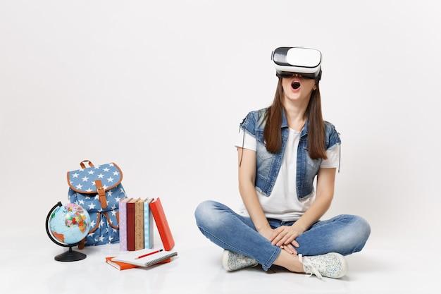 Молодая возбужденная студентка с открытым ртом в очках виртуальной реальности наслаждается сидением возле школьных учебников с рюкзаком-глобусом, изолированными на белой стене