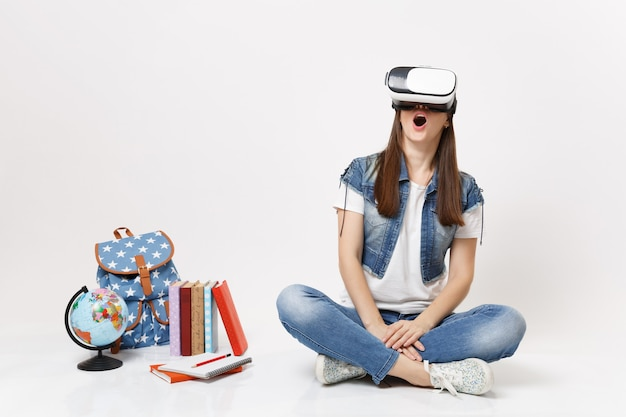 Young excited woman student with opened mouth in virtual reality glasses enjoying sitting near globe backpack school books isolated on white wall