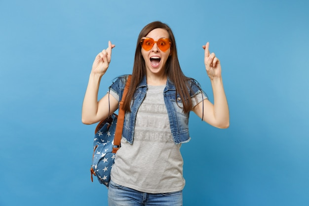 Young excited woman student with opened mouth wearing orange heart glasses waiting for special moment, keeping fingers crossed isolated on blue background. education in high school. advertising area.