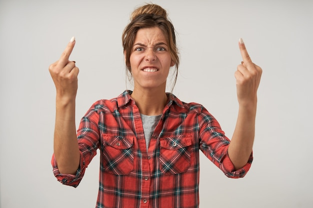 Young excited woman with bun hairstyle doing fuck you bad expression, frowning with pout and raising hands with middle fingers, isolated on white