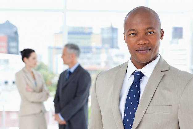 Young executive in a suit standing upright while his team is behind him