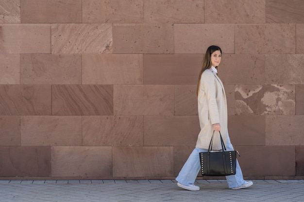 Young executive woman walking in sneakers with coat and handbag