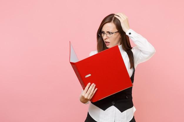 안경을 쓴 젊은 지친 비즈니스 여성은 분홍색 배경에 격리된 머리에 달라붙는 서류 문서를 위해 빨간색 폴더를 보고 있습니다. 여사장님. 성취 경력 부입니다. 광고 공간을 복사합니다.