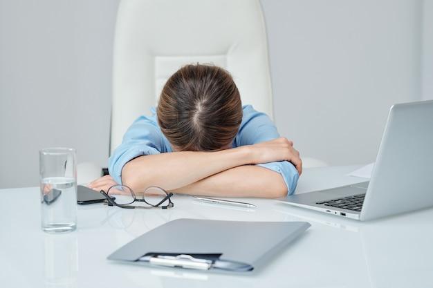 사무실의 안락의자에 앉아 휴식을 취하거나 낮잠을 자는 동안 책상에 팔짱을 끼고 머리를 잡고 있는 지친 젊은 여성