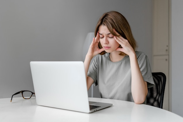 Young exhausted caucasian woman staring at laptop in the apartment