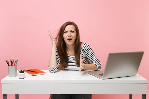 パステルピンクの背景に分離された現代的なpcラップトップで白い机に座って、困惑を広げている手で疲れ果てた若いイライラした女性。業績ビジネスキャリアコンセプト。スペースをコピーします。