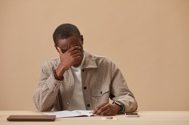 Young exhausted man sitting at the table doing hard work against the beige wall