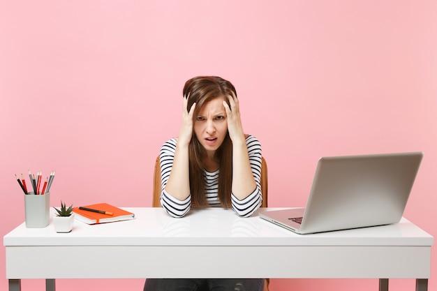 パステルピンクの背景に分離された現代的なpcのラップトップで白い机に座って仕事をしがみつくのに苦労している若い疲れ果てた悲しい女性。業績ビジネスキャリアコンセプト。スペースをコピーします。