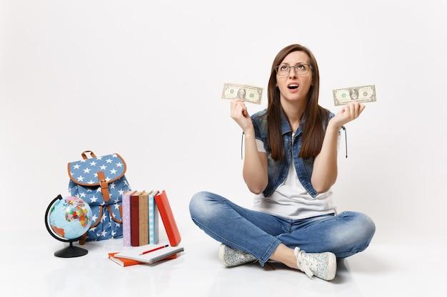 La giovane studentessa esausta che cerca tenendo in mano banconote da un dollaro ha problemi con i soldi si siede vicino al globo, zaino, libri di scuola isolati