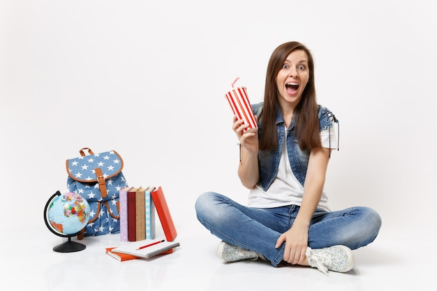 Young exited woman student with opened mouth holding plastic cup of soda or cola sitting near globe, backpack, school books isolated on white wall