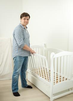 Молодой будущий отец собирает кровать для своего будущего ребенка
