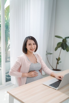Young expectant lady surfing net, remote working, buying goods for newborn