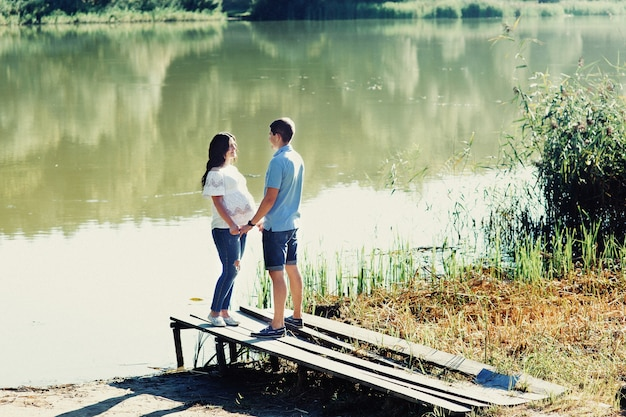 Young expecting couple stands on the bridge by the green river