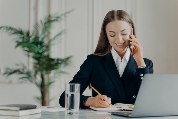 電話で話し、クライアントと通信しながらメモ帳で鉛筆でメモを書く、エレガントな黒のスーツを着た若い経験豊富なビジネスコンサルタント、職場でラップトップに取り組んでいる女性マネージャー