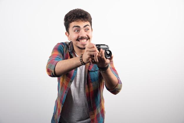 Молодой опытный фотограф серьезно занимается профессиональным фотографированием.