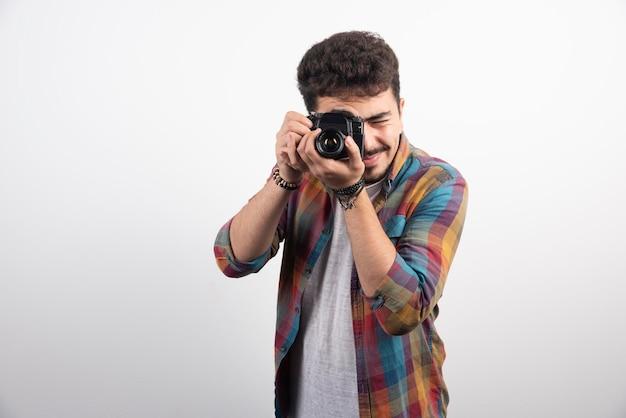 Giovane fotografo esperto che scatta foto professionali in modo serio.