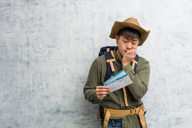 Young explorer chinese man holding an air tickets biting nails, nervous and very anxious