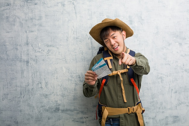 Young explorer chinese man holding an air tickets cheerful and smiling pointing to front