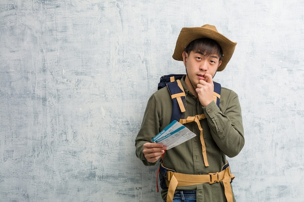 航空券を持っている若い探検家中国人男性は、コピースペースを見ている何かについて考えてリラックスしました
