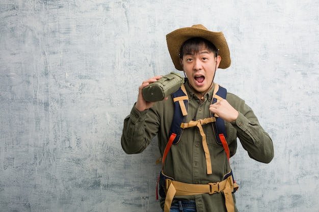 Young explorer chinese man surprised, feels successful and prosperous