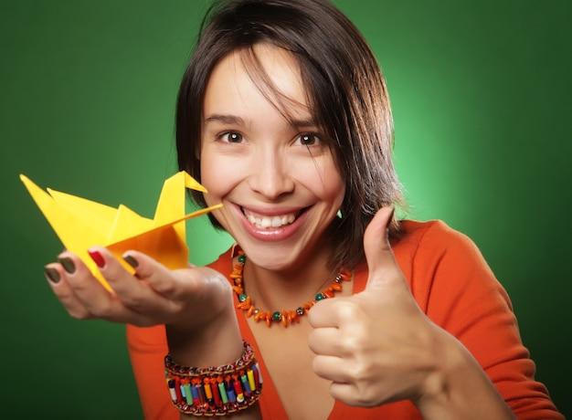 Молодая женщина выражения с бумажной птицей над зеленой стеной