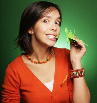 Молодая женщина выражения с бумажной птицей над зеленым