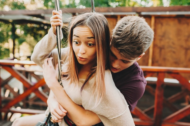 Young expressive shocked woman with boyfriend behind wearing harnesses and hanging on cable of zip line in park